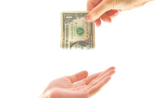 hand giving money to another