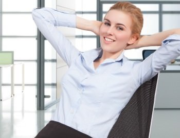 Happy young businesswoman relaxing on chair